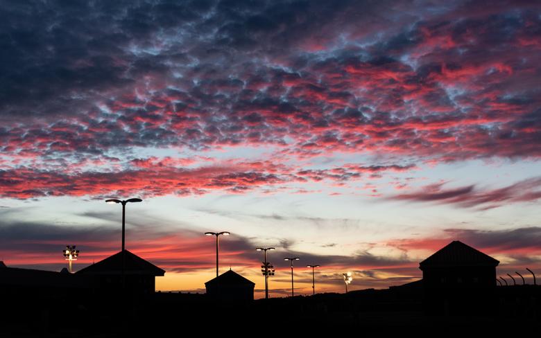 Zonsondergang (Parkeergarage) - Na een filmbezoek aan The Incredibles 2, zag ik een kleurrijke zonsondergang. Ik heb de afleidende lichtjes in de silh