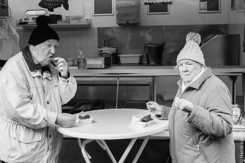 Warmer Fisch bei kaltem Wetter - Duitse toeristen snacken wat kibbeling weg op een koude zaterdag in de stad Groningen (Vismarkt). Nederlanders trouwe