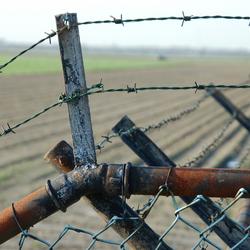 Roestig hek en prikkeldraad