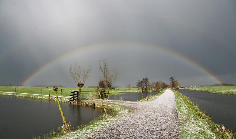 Maartse bui - een maartse hagelbui gevolgd door de zon maakt een mooie regenboog boven de witte polderweg.<br /> groeten, Bert