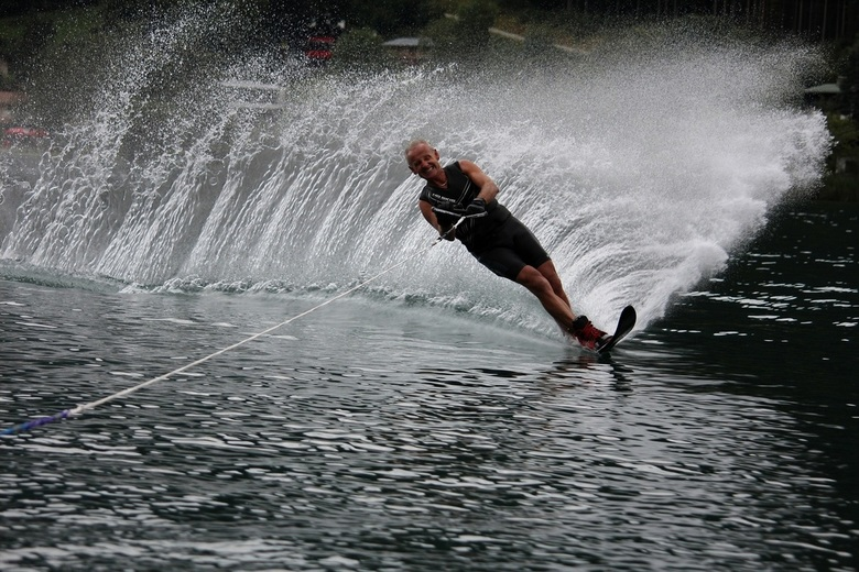 waterski - de actie van de man waterskiend op het water, laat de inspanning van hem zien en tevens het mooie waterballet wat hierdoor ontstaat.