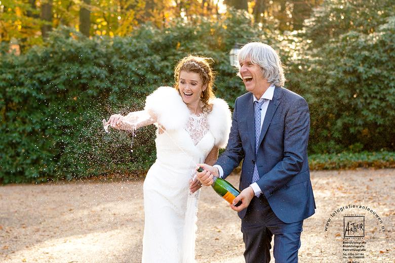 Bruidsfotograaf-Fotografie-Arthur-van-Leeuwen_DSC0132 - Bruidegom spuit met een fles champagne en de bruid vangt het op met een glas.<br /> <br /> N