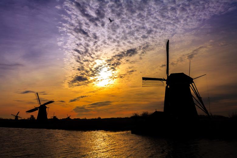 Het silhouette van Kinderdijk - Silhouette van de molens bij Kinderdijk. De zon kroop net achter deze wolken die een lijn vormde die het oog in de fot