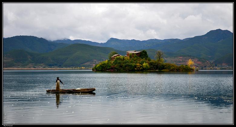 Visser op Lugu lake - In China ligt dit prachtige Lugulake. Hoog in de bergen verstopt, maar niet voor lang meer. Momenteel wordt er gebouwd aan een n