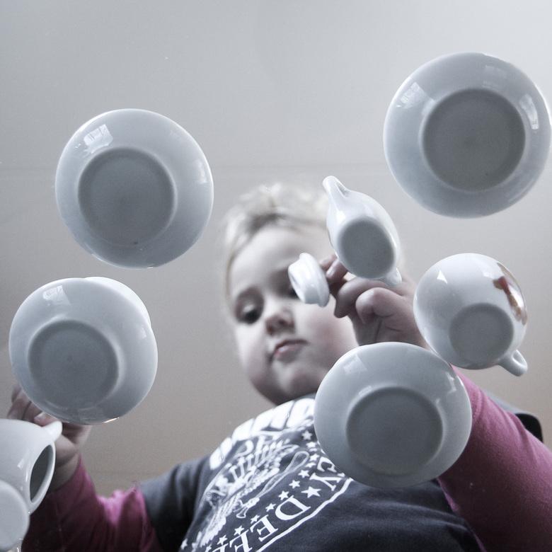 Spelen met het theeservies - diepe concentratie terwijl ze met haar theeserviesje speelt. gefotografeerd van onder een glazen tafel