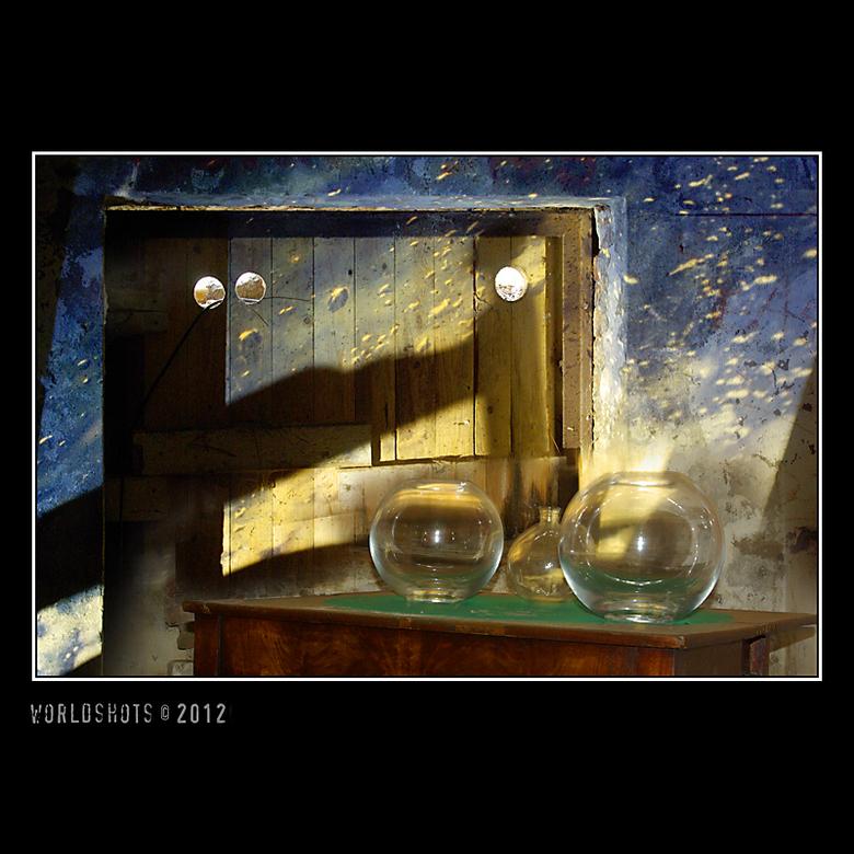 Stil even - Oerol, Terschelling<br /> Stilleven in een bunker, glazen vazen op een tafel verlicht door de projectie van een dia op een houten luik.