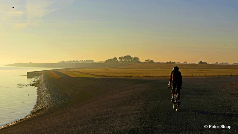 Mountainbiker in de gloed van zonsopgang langs het Wad bij Stroe.  - Mountainbiker in de gloed van zonsopgang langs het Wad bij Stroe.