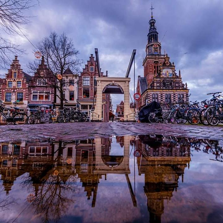 Reflectie de waag - Oud stukje Alkmaar reflecteerde in een plas regenwater. De Waag en de bathbrug en links een stukje Mient.