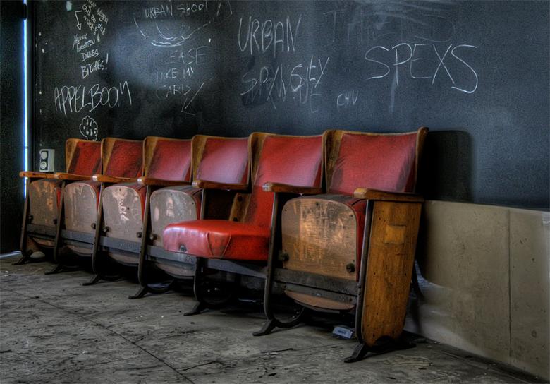 gevolg van verval kun je nauwelijks onder stoelen of banken steken - theaterstoelen met op de achtergrond gekalkt wat urbexers naast hun voetstappen n