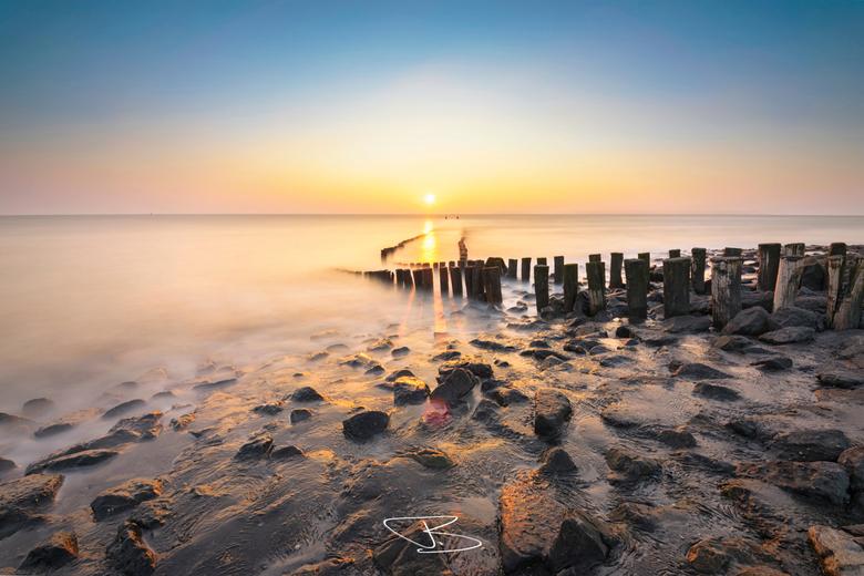 Stay - Een heldere zonsondergang aan de dijk van Westkapelle. Door de lange sluitertijd lijken de golven tot een mist te vormen.