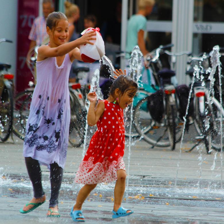 Verkoeling - In de hitte zoeken naar verkoeling. Kinderen doen dat op deze manier. Zonder zorgen, rennend door de fonteintjes spelend met het water. V