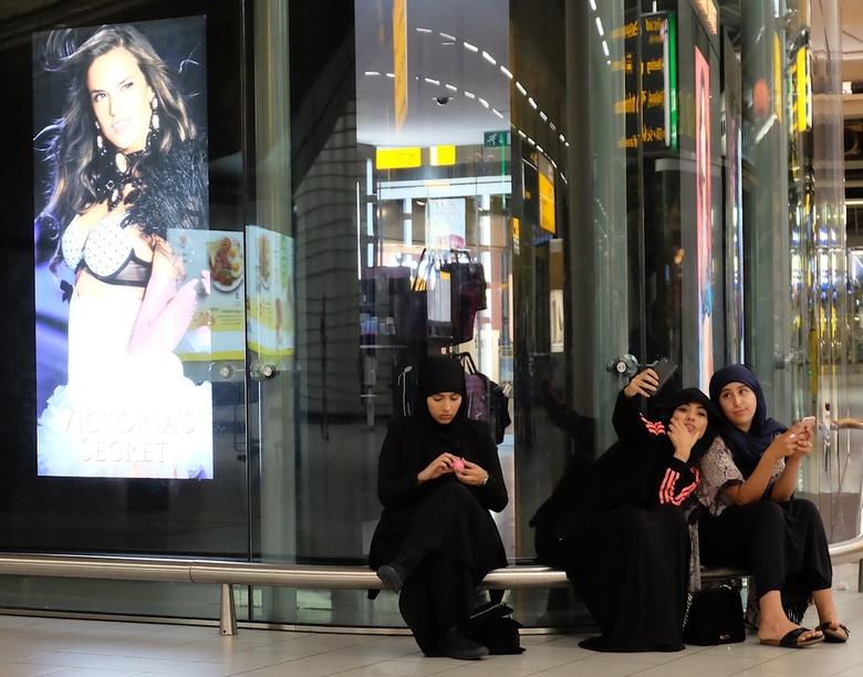 discrepantie - Drie meiden die blijkbaar moslims zijn hebben plezier voor tien met hun mobiel. Selfies maken, appen, reacties delen, kortom, zich tota