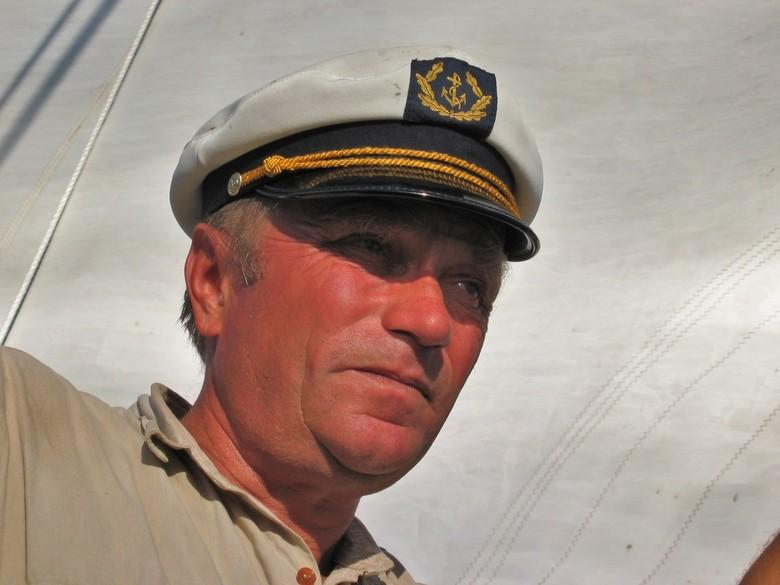Kapitein - Portret van de kapitein tijdens de zeiltocht bij Nidia met als achtergrond het Zeil van de boot.