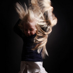 4 years old girl, with her long hair in the air