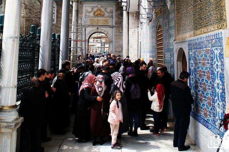 Verveling in de drukte - In de drukte van de Sultan Eyüp - Moskee, kijkt een jong meisje verveeld om haar heen.