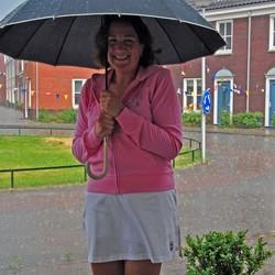 Buurvrouw in zomers regenbuitje