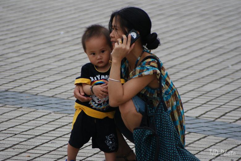 Chinese dame met haar kind - Deze foto heb ik gemaakt op een plein in China Pingnan. Deze dame in gesprek aan de telefoon terwijl haar zoontje bij haa