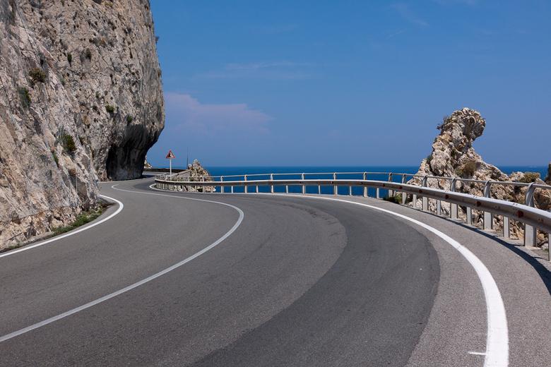 Noli Italië - Rijden langs de rotsen richting het plaatsje Noli in Italië