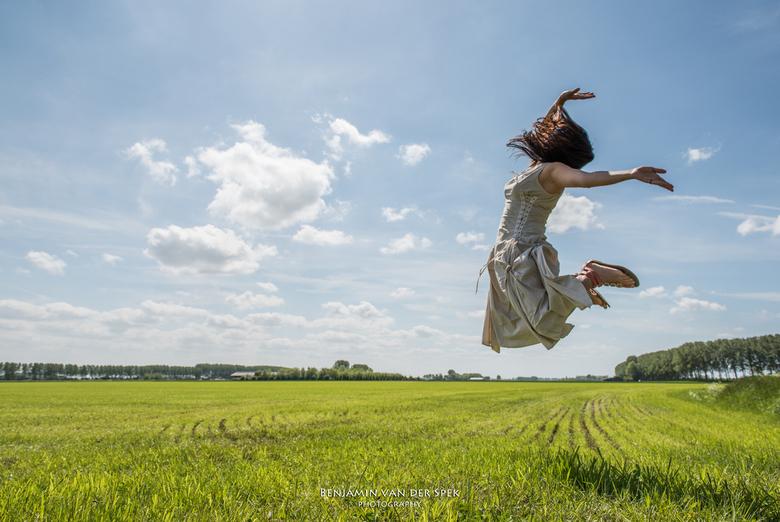 Zeeuws Vlaanderen - Een vrouw springt hoog de lucht in boven het vlakke Zeeuws Vlaamse land.