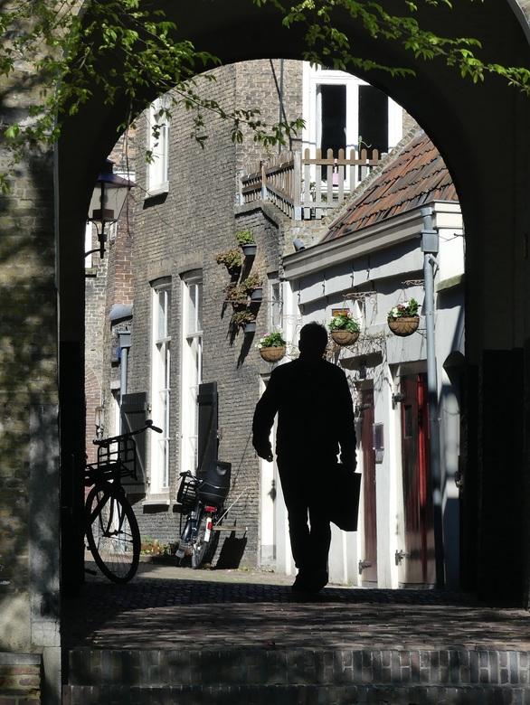 centrum Dordrecht - Man met tas wandelt door het oude centrum van Dordrecht.