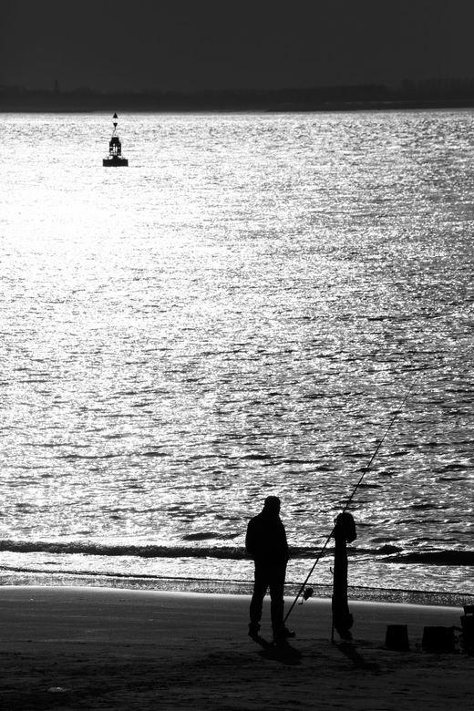 Beet ! - Tijdens de laatste viswedstrijd van dit jaar (2015) staat een visser op het strand van Vlissingen geduldig te wachten tot hij beet krijgt. Na