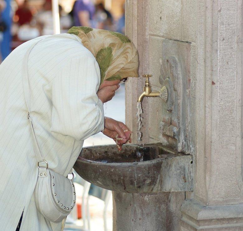Tandjes poetsen - Een vrouw in turkije die bij een openbare watervoorziening even de tanden spoelt.