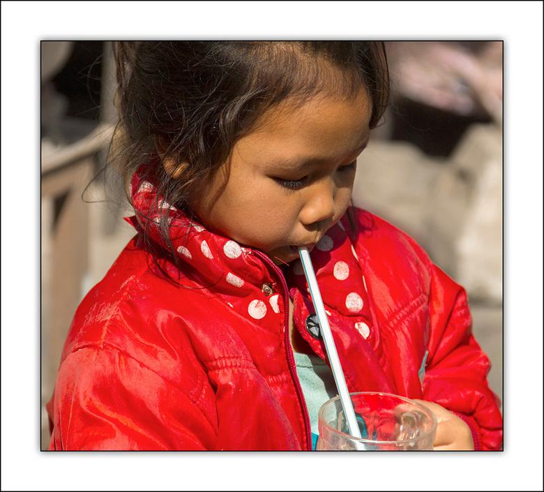 dorst lessen - meisje in Laos volledig verdiept in haar glas met drinken