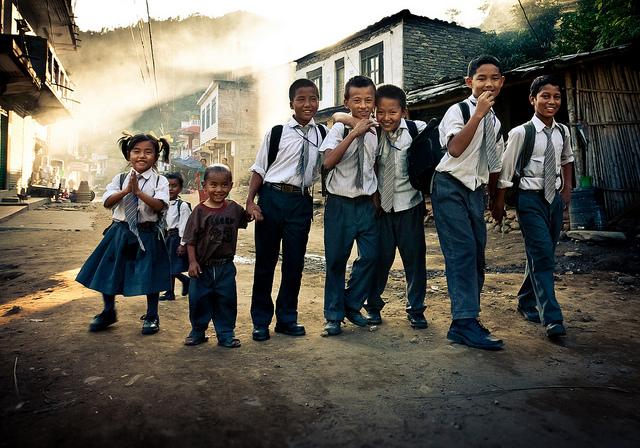 Schoolkinderen Nepal - Tijd om naar school te gaan voor de kinderen in het bergdorp in Nepal. Het ochtendlicht schijnt laag tussen de bergen door wann