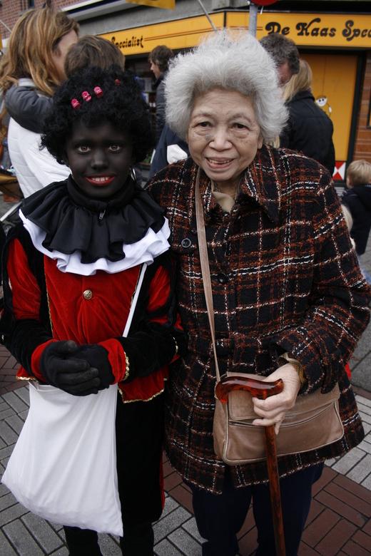 """Jong - Een vrouw, weer kind als ze zwarte Piet en Sinterklaas ontmoet. Lachend rent ze achter ze aan: """"Sinterklaas! Zwarte Piet! Mag een oude oma"""
