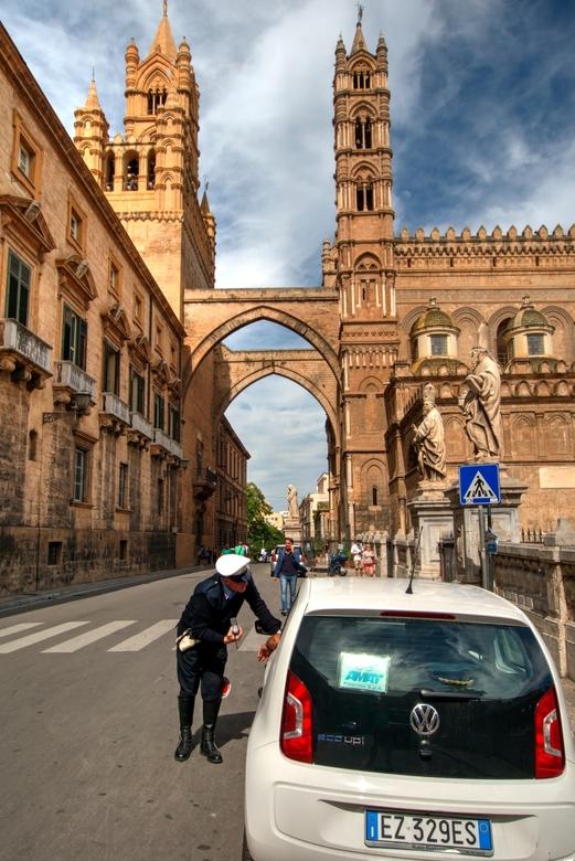 Onder het wakend oog... - In het centrum van Palermo spreekt heer agent de chauffeur van de Up toe. Nabij staat de basiliek, met rondom het plein beel