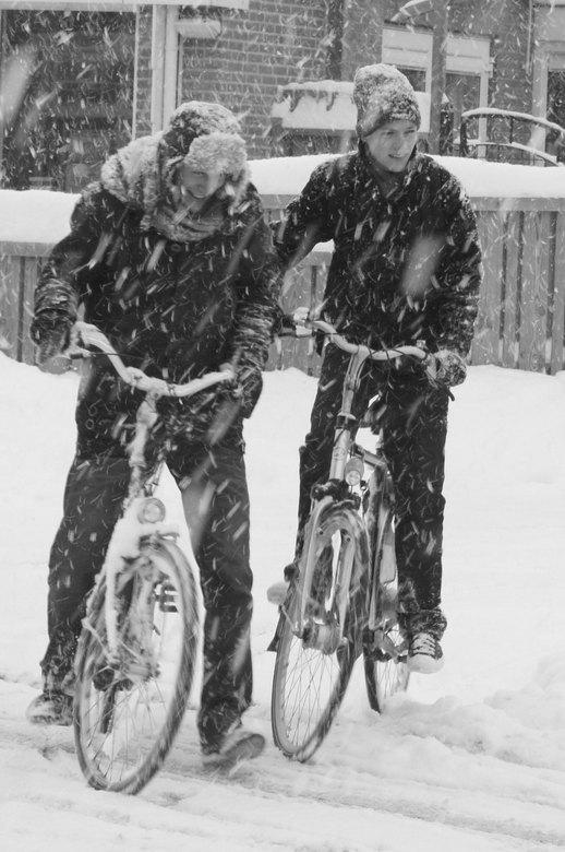 Sneeuwpret - Toen ik met mijn toestel in de erker van de buurman stond te schuilen zag ik deze scholieren die dapper genoeg waren om zich op de fiets