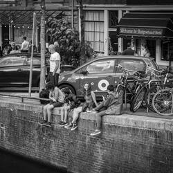 Kinderen chillen aan de gracht in Amsterdam