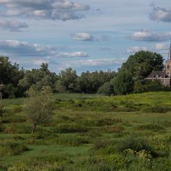 Landschap met kerkje en ooievaars