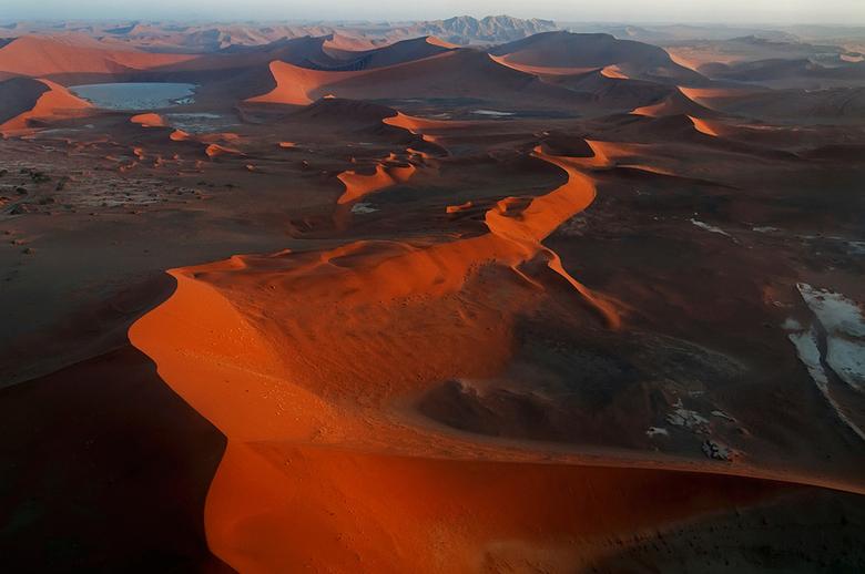 Vergezicht Sossusvlei - Luchtfoto van de Sossusvlei in Namibië. Links bovenin is nog net deadvlei te zien. Mooie schaduwwerking in het landschap door