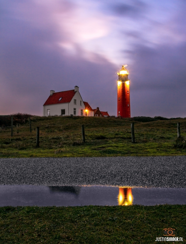 Vuurtoren van Texel tijdens stormachtige zonsondergang.