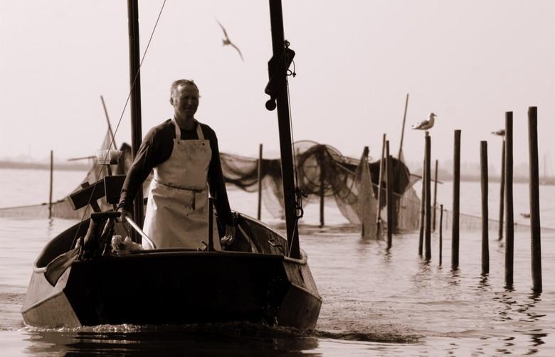 Ambacht... - Friesland. Een visserman die zijn netten uit het water kwam halen. Hij had 16 van die plekken in het meer en had nu wel het hijsen van di