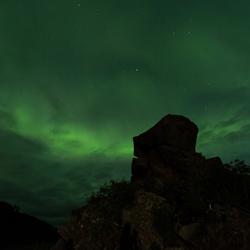 Noorderlicht achter een hoofdvormige rots op de Lofoten