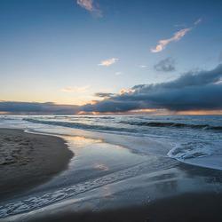 Het Egmondse strand met een bewolkte ondergaande zon