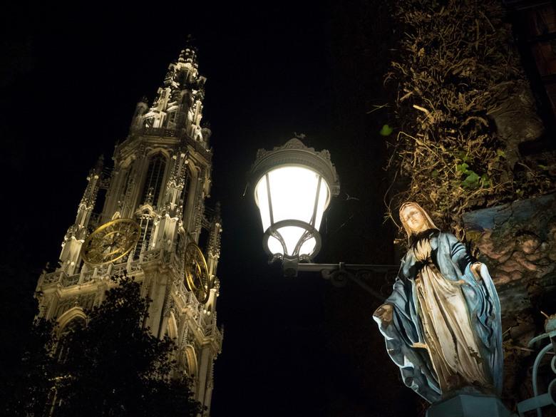 """Antwerp by night - De Antwerpse Onze-Lieve-Vrouwekathedraal toren met heiligenbeeld en lantaarn tegen gevel café """"Elfde gebod"""""""