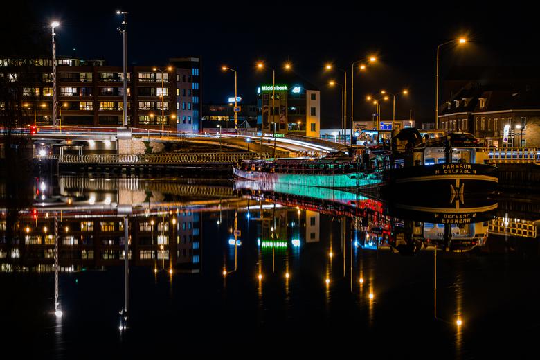 Reflecties op wachtend schip - Het rood en groen van de verkeerslichten reflecteren op het water en het schip, dat in het donker ligt te wachten tot d