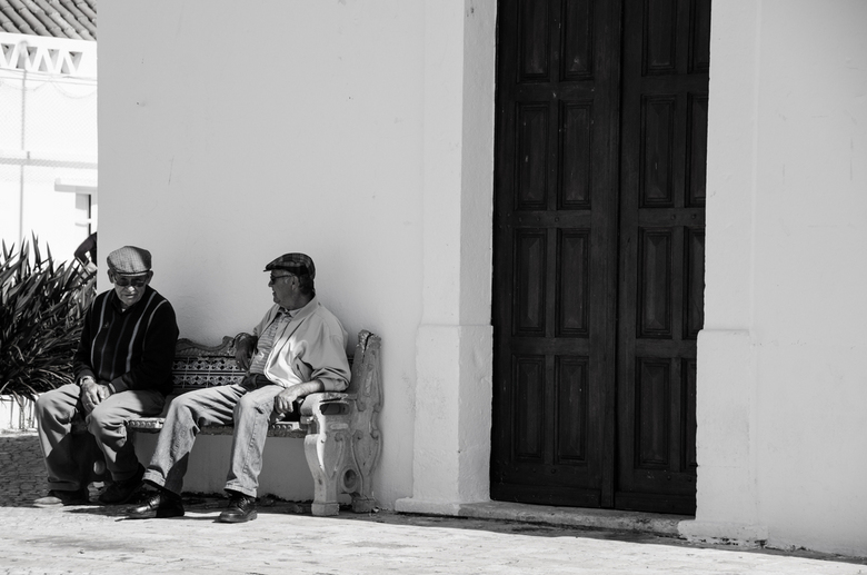 bijpraten - Deze 2 mannen bespreken hun dag voor een kerkje in Armacao de Pera. Hoe onopvallend ik ook probeerde te zijn...mijn camera viel de linker
