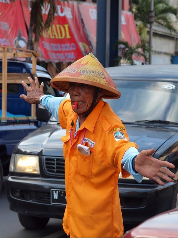 De parkeer regelaar - In de drukte van de steden in Indonesië is een parkeer regelaar onontbeerlijk. <br /> Hier zo een regelaar aan het werk in Sura