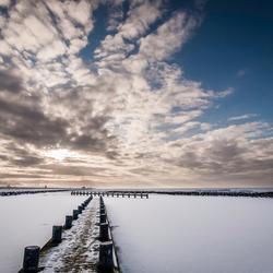 Het bevroren Markermeer vanf een steiger.