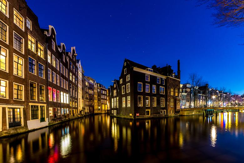 De grachtengordel in avondlicht - Amsterdam in het avondlicht. In Amsterdam voelt het of de tijd heeft stil gestaan. Op de foto zie je de Voorburgwal
