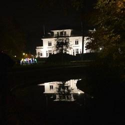Weerspiegeling van verlicht huis