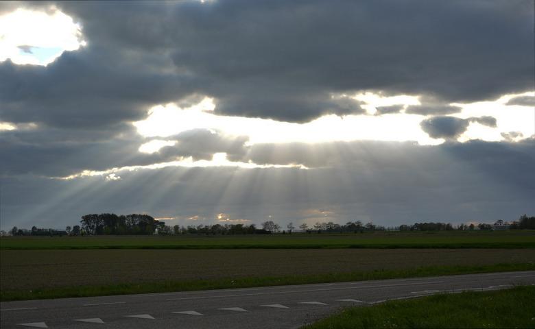 Donkere wolken en Jacobsladders boven Kantens. - Donkere wolken en Jacobsladders boven Kantens.