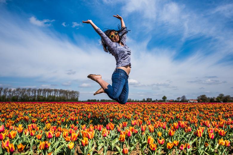 Uit de Zeeuwse klei - Een vrouw springt hoog en blij uit een veld met oranje tulpen.