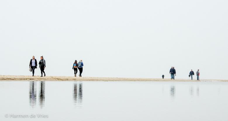 Walking on the edge - Wandelen tussen Nederland en de horizon dankzij water in de plassen op de voorgrond die bij eb zijn ontstaan, de Noordzee achter
