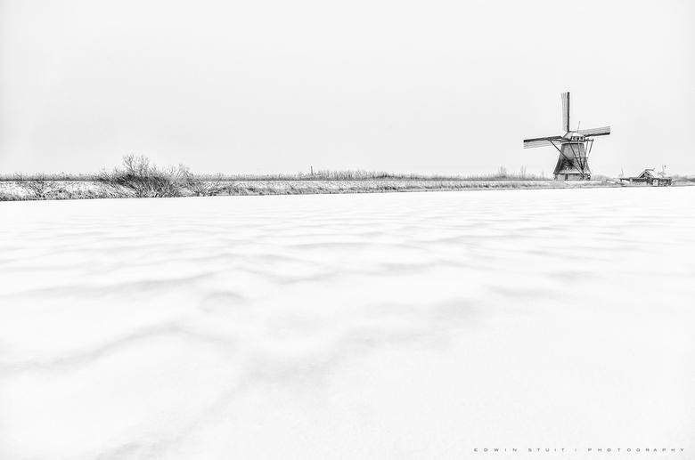 Hollands sneeuwlandschap - Kinderdijk bedekt onder een sneeuwlaag.