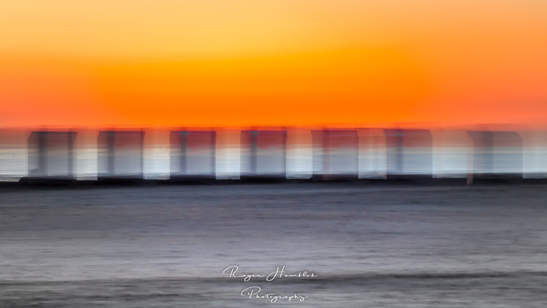 Transparante strandcabines in de avondzon. - Transparante strandcabines, dicht bij de zee, in een warme avondgloed.
